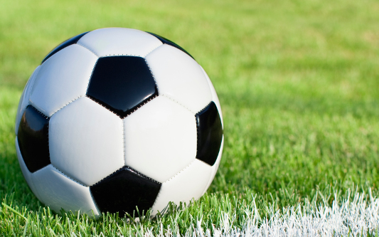A traditional soccer ball sits on a grass field with white stripe